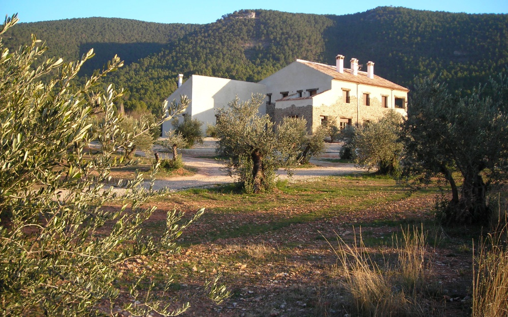 "Rural hotel "" Cortijo la Agedrea"" located in a valley, surrounded by pine trees and mountains"